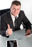 Hombre de negocios joven entusiasta que muestra el pulgar para arriba Foto de archivo