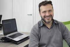 Hombre de negocios joven feliz, desarrollador de software, técnico del ordenador que trabaja en oficina moderna fotografía de archivo libre de regalías