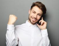 Hombre de negocios joven feliz en camisa que gesticula y que sonríe mientras que t Fotografía de archivo