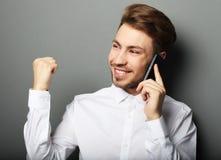 Hombre de negocios joven feliz en camisa que gesticula y que sonríe mientras que t Imagen de archivo
