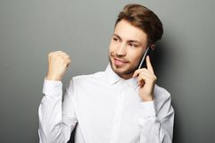 Hombre de negocios joven feliz en camisa que gesticula y que sonríe mientras que t imagen de archivo libre de regalías