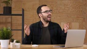 Hombre de negocios joven feliz ilooking en el ordenador portátil emocionado por las buenas noticias, triunfo, victoria almacen de video
