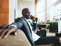 Hombre de negocios joven feliz que espera en el pasillo del hotel que hace un teléfono Ca Fotos de archivo