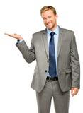 Hombre de negocios joven feliz que muestra el copyspace vacío en el backgro blanco Fotos de archivo