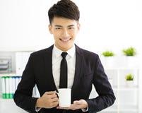 Hombre de negocios joven feliz que se relaja en oficina fotografía de archivo