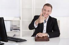 Hombre de negocios joven feliz que se sienta en su oficina que hace el pulgar encima de la GE imágenes de archivo libres de regalías