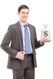 Hombre de negocios joven feliz que sostiene un bolso con la muestra de dólar de EE. UU. Fotografía de archivo