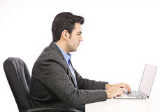 Hombre de negocios joven feliz que trabaja en el ordenador portátil Foto de archivo