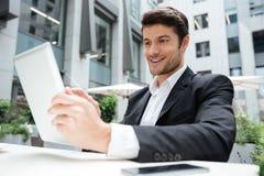 Hombre de negocios joven feliz usando la tableta en café al aire libre Fotos de archivo