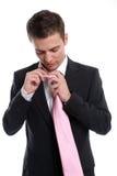 Hombre de negocios joven, fijando su lazo Imagen de archivo