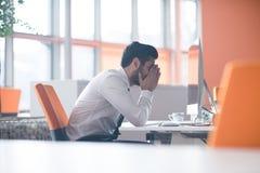 Hombre de negocios joven frustrado en el trabajo Foto de archivo