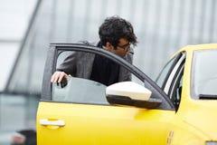 Hombre de negocios joven Getting In Taxi foto de archivo