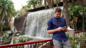 Hombre de negocios joven hermoso al aire libre, resbalando la pantalla táctil del smartphone, cascada almacen de metraje de vídeo