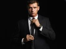 Hombre de negocios joven hermoso que ajusta el suyo lazo Hombre joven en juego imagenes de archivo