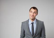 Hombre de negocios joven hermoso que piensa en fondo gris Imágenes de archivo libres de regalías