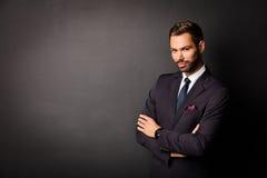 Hombre de negocios joven hermoso que se coloca confiado en negro Foto de archivo libre de regalías