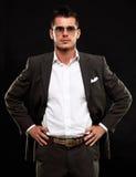 Hombre de negocios joven hermoso que se coloca en negro Imagen de archivo libre de regalías
