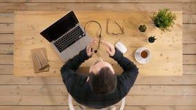 Hombre de negocios joven hermoso que se sienta en el escritorio de oficina con el ordenador portátil y que habla con alguien almacen de video