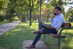 Hombre de negocios joven hermoso que trabaja en su ordenador portátil en el parque imagenes de archivo