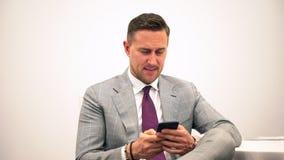 Hombre de negocios joven hermoso que usa la chaqueta feliz sonriente del traje del smartphone que lleva Hombre de negocios usando metrajes