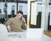 Hombre de negocios joven hermoso usando el teléfono elegante en oficina Foto de archivo libre de regalías
