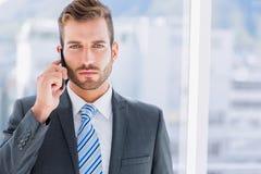 Hombre de negocios joven hermoso usando el teléfono móvil Fotos de archivo libres de regalías