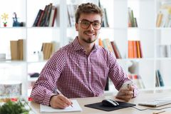 Hombre de negocios joven hermoso usando su teléfono móvil en la oficina Imagen de archivo