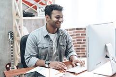 Hombre de negocios joven indio Work en el ordenador en la tabla imagenes de archivo