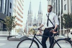 Hombre de negocios joven Looking in camera que monta en la bici imagen de archivo libre de regalías