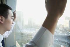 Hombre de negocios joven Looking hacia fuera la ventana en Pekín Fotografía de archivo libre de regalías