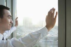 Hombre de negocios joven Looking hacia fuera la ventana en Pekín Imagen de archivo libre de regalías