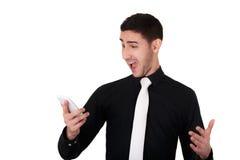 Hombre de negocios joven Looking Surprised en su teléfono elegante fotos de archivo