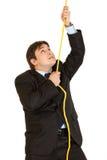 Hombre de negocios joven obstinado que sube para arriba en cuerda fotos de archivo