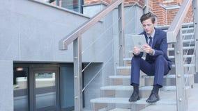 Hombre de negocios joven Online Video Chat, sentándose en las escaleras fuera de la oficina almacen de video