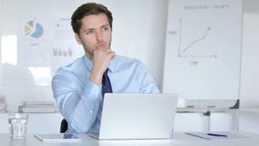 Hombre de negocios joven de pensamiento que trabaja en el ordenador port?til almacen de metraje de vídeo
