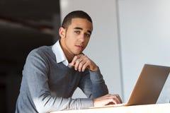 Hombre de negocios joven pensativo en el ordenador portátil Fotos de archivo libres de regalías