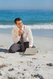 Hombre de negocios joven pensativo que se sienta en la arena con su ordenador portátil fotos de archivo libres de regalías