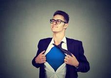 Hombre de negocios joven que actúa como un superhéroe que rasga su camisa apagado imágenes de archivo libres de regalías