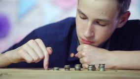 Hombre de negocios joven que apila monedas Cierre para arriba almacen de video