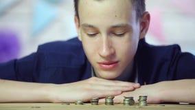 Hombre de negocios joven que apila monedas Cierre para arriba metrajes