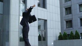 Hombre de negocios joven que aumenta las manos para arriba, triunfo del ganador, satisfacción con resultado metrajes