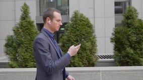 Hombre de negocios joven que camina abajo de la calle con los auriculares inalámbricos y escribir un mensaje en el smartphone