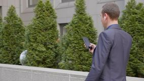 Hombre de negocios joven que camina abajo de la calle con los auriculares inal?mbricos y escribir un mensaje en el smartphone metrajes