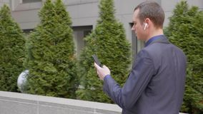 Hombre de negocios joven que camina abajo de la calle con los auriculares inal?mbricos y escribir un mensaje en el smartphone