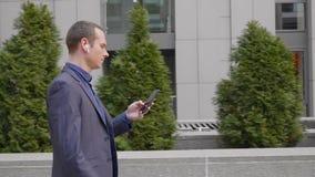 Hombre de negocios joven que camina abajo de la calle con los auriculares inal?mbricos y escribir un mensaje en el smartphone almacen de metraje de vídeo