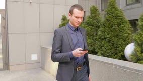Hombre de negocios joven que camina abajo de la calle y escribir un mensaje en el smartphone