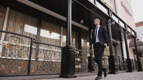Hombre de negocios joven que camina con confianza abajo de la calle almacen de metraje de vídeo
