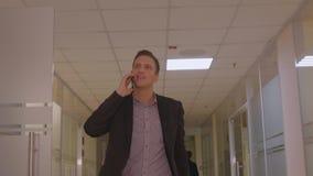 Hombre de negocios joven que camina en la oficina de negocios del pasillo que habla por el teléfono móvil metrajes