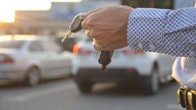 Hombre de negocios joven que camina en parquear la llave a mano al aire libre y que se considera del coche Brazo del hombre de ne metrajes