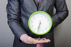 Hombre de negocios joven que celebra el dinero y el reloj Fotografía de archivo